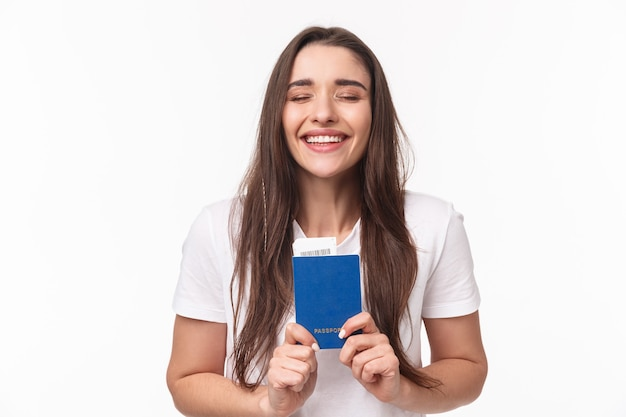 여행, 휴일, 여름 개념. 행복하고 꿈꾸는 소녀의 클로즈 업 초상화가 마침내 여행, 비행기 티켓으로 여권을 들고 행복한 느낌