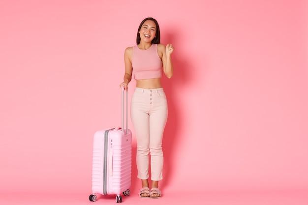 Viaggi, vacanze e concetto di vacanza. a figura intera della ragazza asiatica sorridente allegra che finalmente va all'estero
