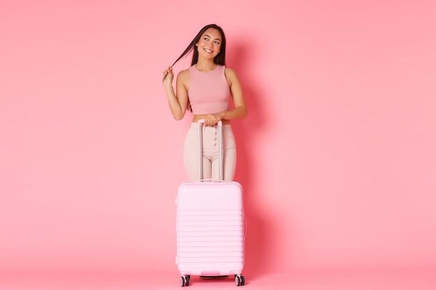 Viaggi, vacanze e concetto di vacanza. a figura intera della ragazza asiatica bruna civettuola sognante in abiti estivi