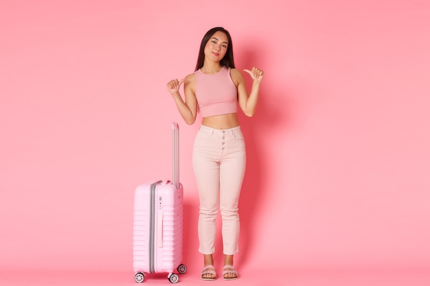 Travelling, holidays and vacation concept. full-length of good-looking asian girl in summer clothes packed bags to go abroad, pointing at herself sassy, planned perfect travel tour, hold suitcase.