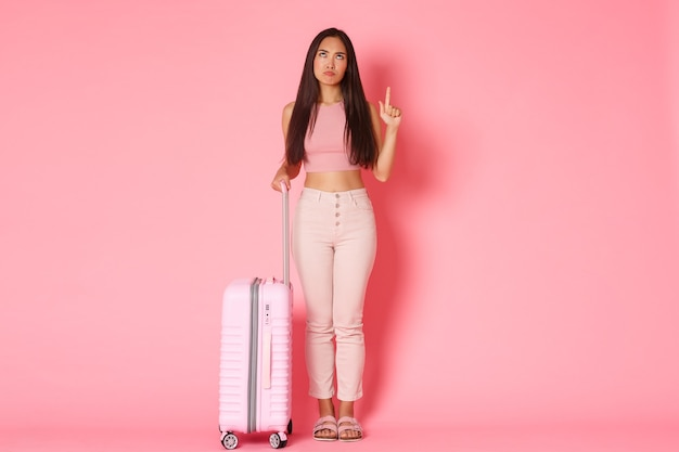 Travelling holidays and vacation concept fulllength of upset and disappointed complaining girl tourist grimacing as looking and pointing finger up frowning angry holding suitcase pink wall
