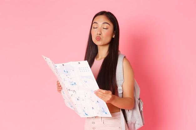 バックパックと地図で愚かなアジアの女の子の観光客の旅行ライフスタイルと観光コンセプトの肖像画...