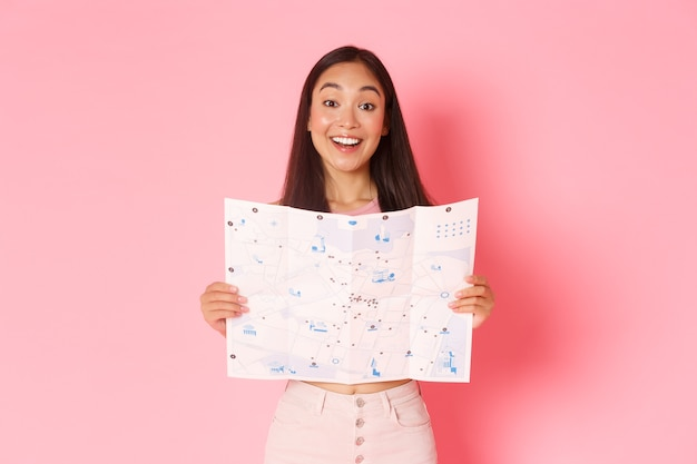Travelling, lifestyle and tourism concept. cheerful, attractive asian girl tourist explore new city, visiting museums, showing map of city with sightseeings and smiling upbeat, pink background.