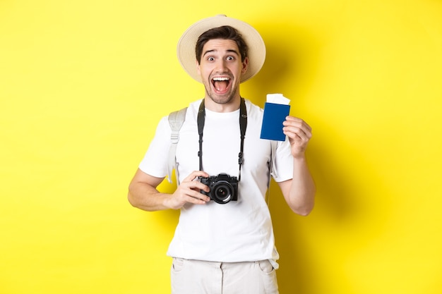 旅行、休暇、観光のコンセプト。チケット付きのパスポートを示し、カメラを持ち、麦わら帽子をかぶって、黄色の背景の上に立っている、excotedtpirost。