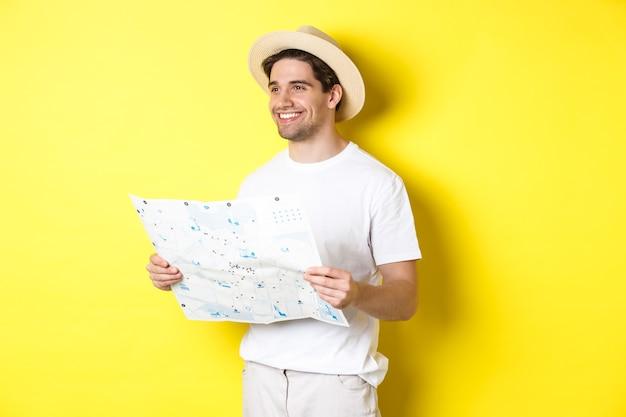 旅行、休暇、観光のコンセプト。観光に行くハンサムな男の観光客、地図を保持し、笑顔、黄色の背景の上に立っています。