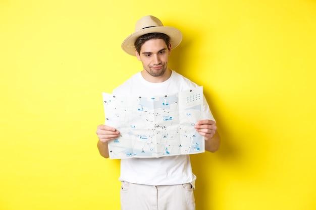 旅行、休暇、観光のコンセプト。黄色の背景の上に立って、正しい方向を探して、地図で混乱している探している男性の観光客。