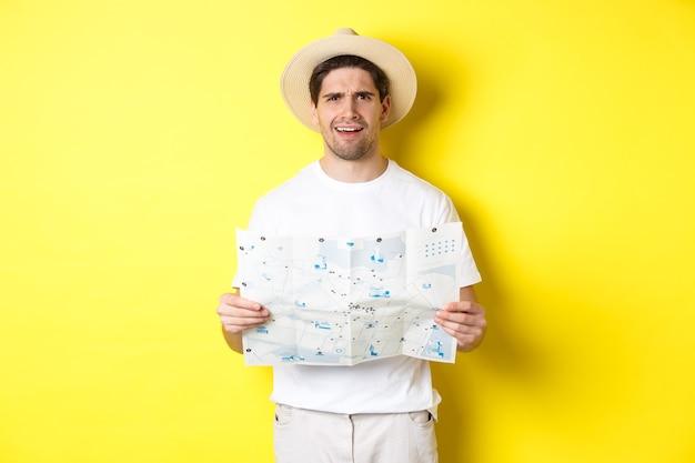旅行、休暇、観光のコンセプト。困惑した男の観光客は地図を理解できず、カメラを見て混乱し、黄色の背景に立っています