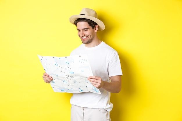 旅行、休暇、観光のコンセプト。黄色の背景に立って、観光と地図を見て幸せな観光客の笑顔
