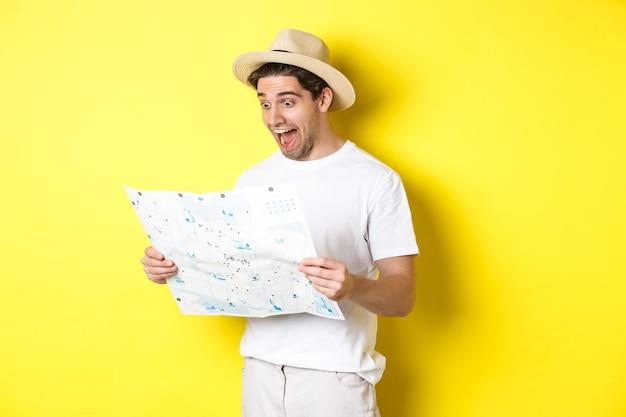 旅行、休暇、観光のコンセプト。黄色の背景に立って、観光と地図を見て幸せな観光客の笑顔。