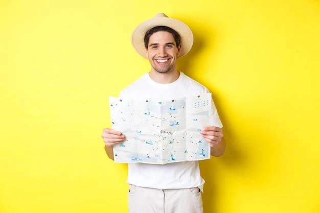 旅行、休暇、観光のコンセプト。旅行に行く笑顔の若い男、ロードマップを保持し、笑顔、黄色の背景の上に立っています。