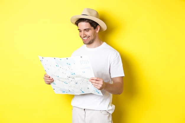 Concetto di viaggio, vacanza e turismo. sorridente turista felice guardando la mappa con visite turistiche, in piedi su sfondo giallo