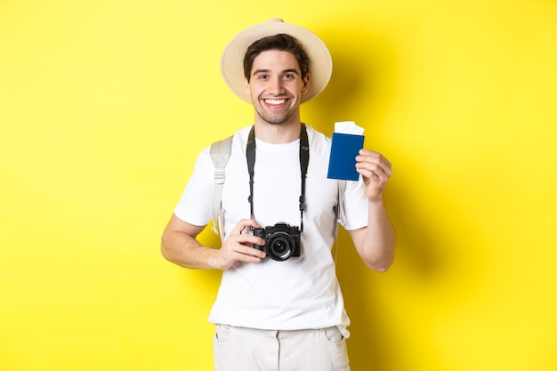Concetto di viaggio, vacanza e turismo. sorridente turista che tiene la macchina fotografica, mostrando il passaporto con i biglietti, in piedi su sfondo giallo