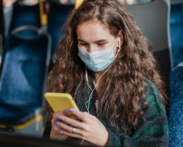 バスで旅行し、保護マスクを着用する