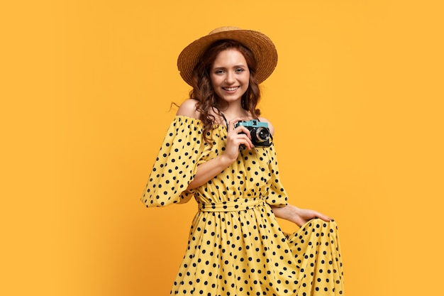 Путешествующая женщина в соломенной шляпе и летнем платье позирует с ретро-камерой на желтом