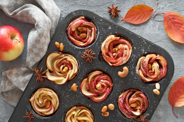 Tray of apple roses baked in puff pastry with autumn leaves and apples on dark
