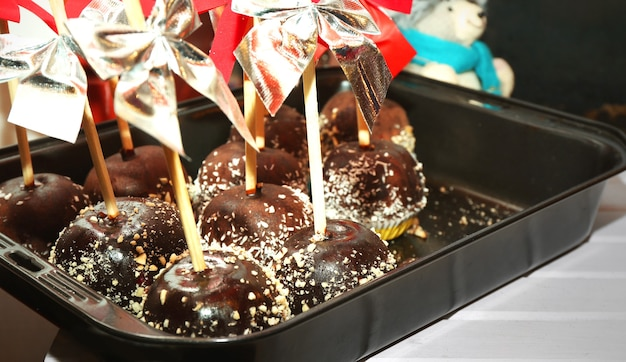 Tray of apples icing with chocolate at christmas food kiosk