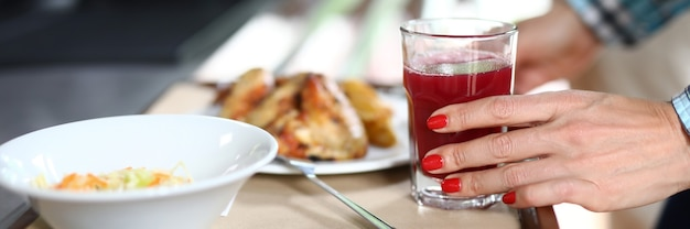 On tray are plates with dinner dishes female hand holds glass of red liquid