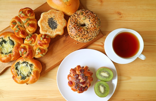 Tray of assorted buns and cut kiwi fruit with hot tea on wooden table