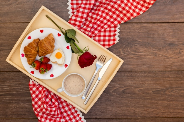Tray of breakfast with red rose