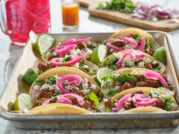 Tray of carne asada tacos topped with pickled onions and cojita cheese