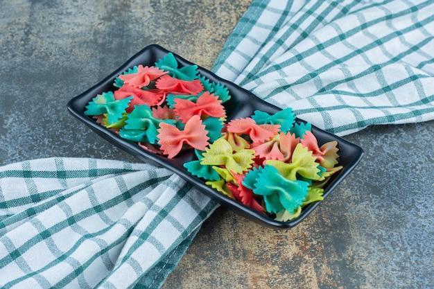 Un vassoio di paste colorate farfalle sull'asciugamano, sulla superficie di marmo.