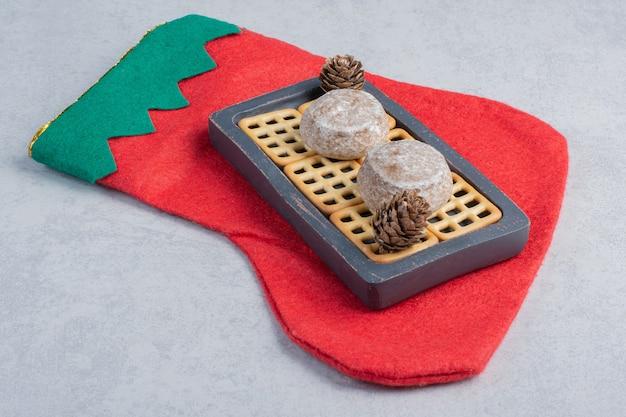 Biscotti e biscotti del vassoio su una calza di natale sulla superficie di marmo