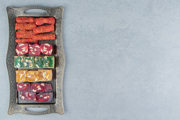 Tray full of appetizing turkish delight on the marble background. high quality photo
