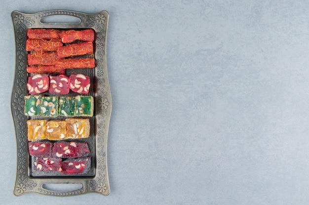 대리석 배경에 식욕을 돋우는 터키 기쁨으로 가득 찬 트레이. 고품질 사진