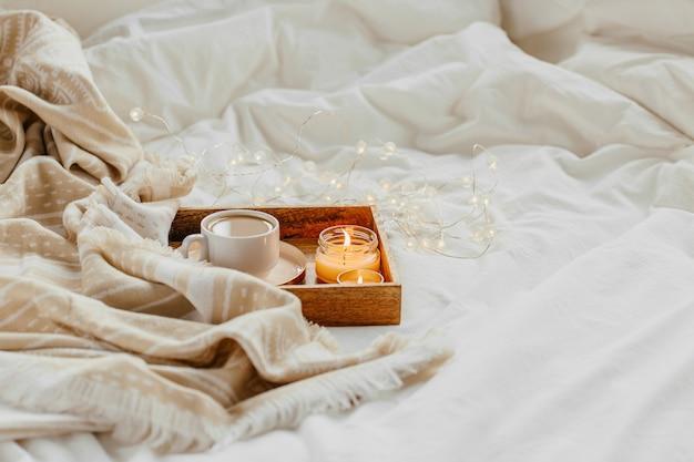 Поднос с кофе и свечами с теплым пледом на белом постельном белье. завтрак в постель. скандинавский стиль. плоская планировка, вид сверху