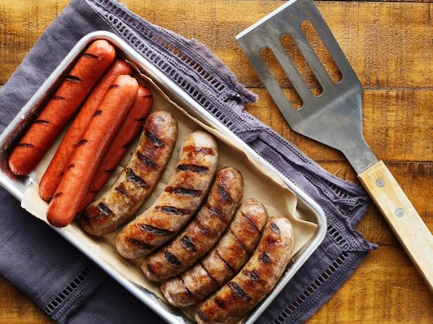 Поднос с жареными хот-догами и колбасками на подносе сверху вниз