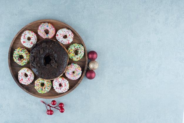 Поднос с маленькими пончиками вокруг одного большого пончика на мраморе.