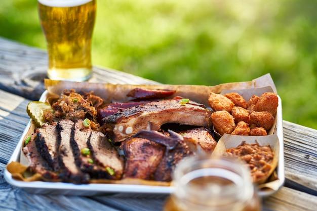 日当たりの良い夏の日のピクニックテーブルの上の外の燻製肉テキサスバーベキュースタイルのトレイ