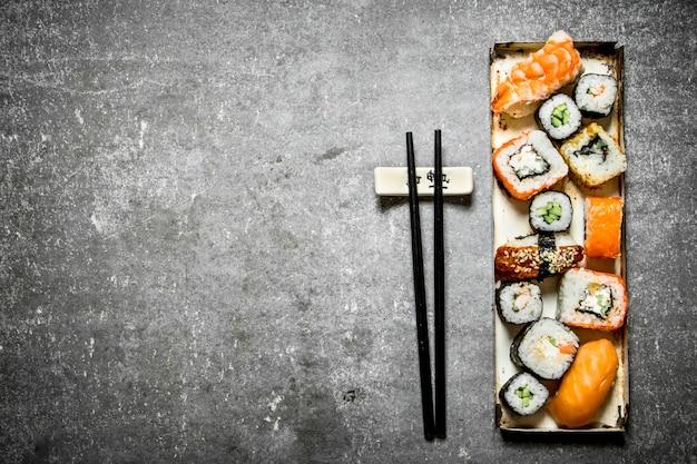 Поднос суши роллов и морепродуктов. на каменном столе.