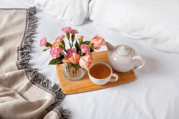 Поднос с чаем на кровати. белые простыни с одеялом и подушкой. завтрак в постель. теплый и уютный скандинавский концепт хюгге - чашка чая.