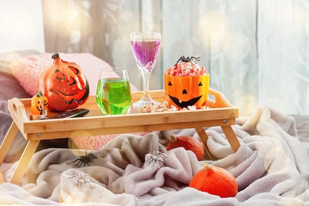 ハロウィーンの装飾、ポップコーン、飲み物、リモコン付きのベッドのトレイ。映画の夜のハロウィーンの背景、休日の娯楽のアイデア