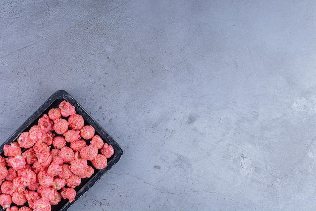 Tray of red popcorn candy on marble surface