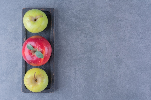 Un vassoio di mele mature sul tavolo di marmo.