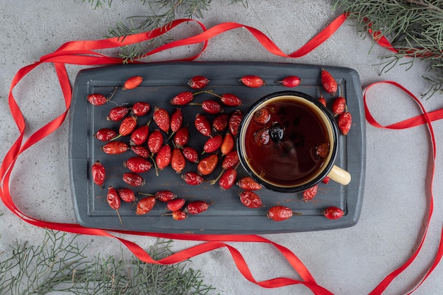 Tray of rose hips and a mug of dog rose tea surrounded with ribbons on marble surface