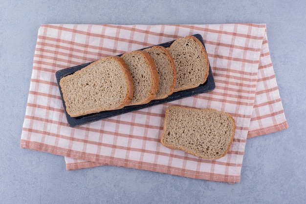 Tray of sliced brown bread on a folded towel on marble surface