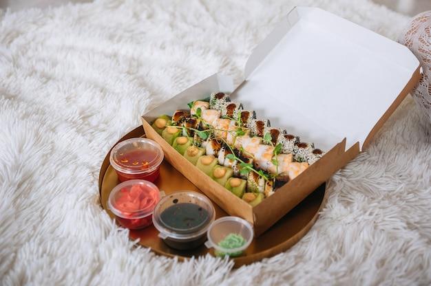 自宅の白いじゅうたんの上に寿司とソースの箱が入ったトレイ。