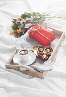 Tray with a cup of coffee flowers and chocolates