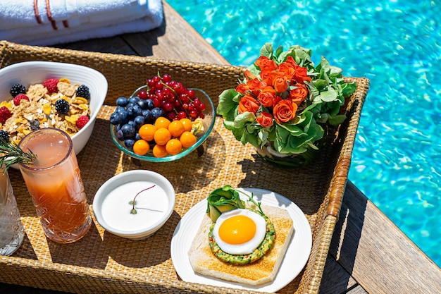 スイミングプールの近くで各種朝食の食事と飲み物をトレイに