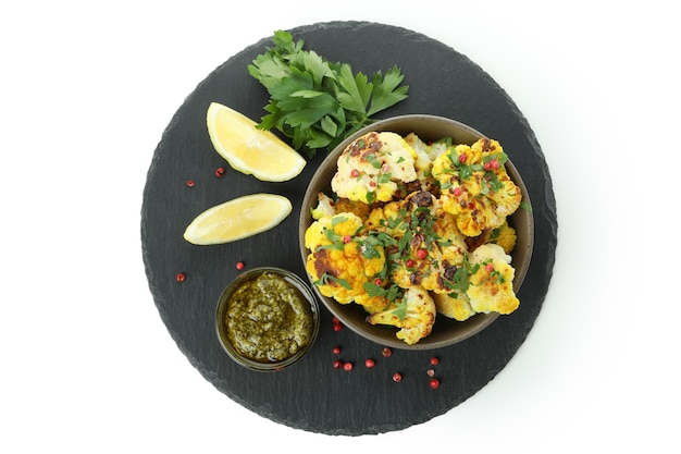 Tray with baked cauliflower and spices isolated on white background.
