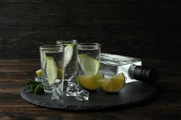 Поднос с бутылкой и рюмками напитка, лайма и льда на деревянной стене