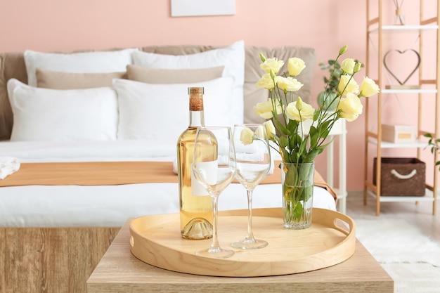 호텔 허니문 룸의 테이블에 와인 병과 안경 트레이