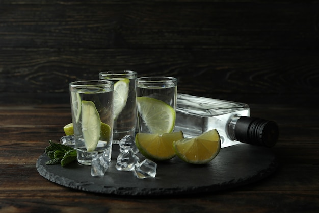 Tray with bottle and shots of drink, lime and ice on wooden wall