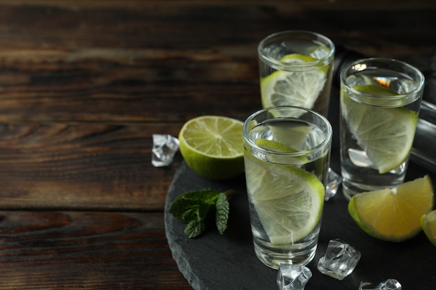 Tray with bottle and shots of vodka, lime and ice on wooden table