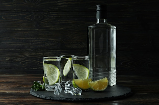 Tray with bottle and shots of vodka, lime and ice on wooden