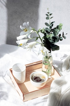 A tray with a bouquet of flowers and coffee on a white bed