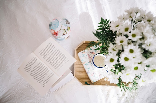 Tray with bouquet near opened book